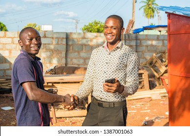 business agent shaking hands with a local carpenter in his workshop
