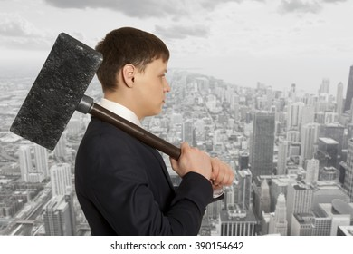 Business aggression. Determined businessman with hammer in hands.