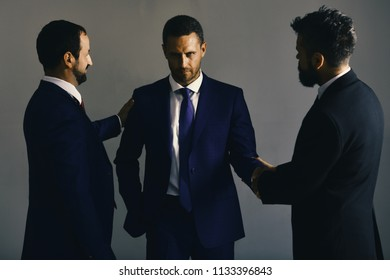 Business agreement and compromise concept. Businessmen wear smart suits and ties. Men with beard and tricky faces negotiate making deal. CEOs settle disputes on light grey background