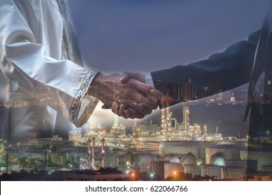 Business agreement concept : Double exposure of handshake with oil refinery factory at night in background.