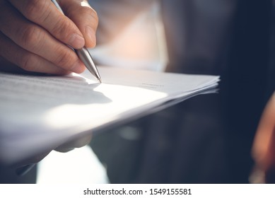 Business agreement, deal concept. Closeup image of Businessman reading official contract before making a deal. Corporate man with pen in hand working in office, signing business document on desk