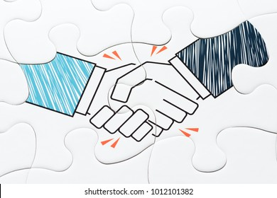 Business agreement. Handshake jigsaw puzzle pieces. Concept image of agreement and corporation.