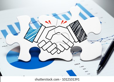 Business agreement. Handshake jigsaw puzzle pieces on report. Concept image of business partnership and agreement.