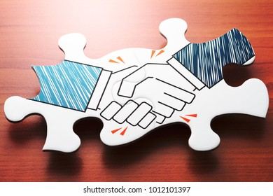 Business agreement. Handshake jigsaw puzzle pieces on wood desk. Concept image of agreement and partnership.