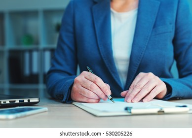 Business agreement signing, businesswoman handwriting signature on contract document at office desk