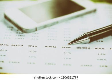 Business analysis - Accounting Calculating Cost Economic on office table. Pencil, chart on papper and bllured smartphone in background