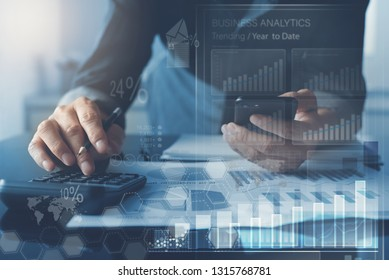 Business analysis, businessman using mobile smart phone, calculator to calculate  business data with financial graph, marketing report and modern computer dashboard interface, virtual screen
