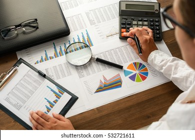 Business analysis - calculator, sheet, graphs (business report) and analyst hand, top view