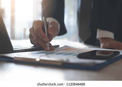 Business analysis concept. Businessman in black suit analyzing business documents, finacial report, working on laptop computer, mobile smart phone on office desk, close up.