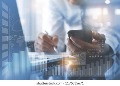 Business analysis concept. Businessman using mobile smart phone, working on laptop computer at modern office with financial graph diagram, business data computer dashboard on virtual screen