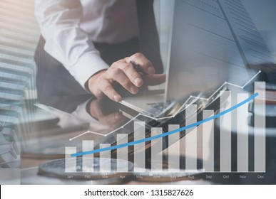 Business analysis, financial investment and economic growth concept. Double exposure of businessman working on tablet computer, analysing financial graph on virtual screen and business building