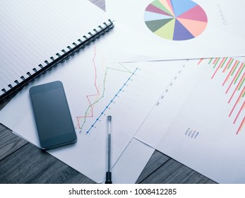 business analysis graphics on table with smart phone and pen