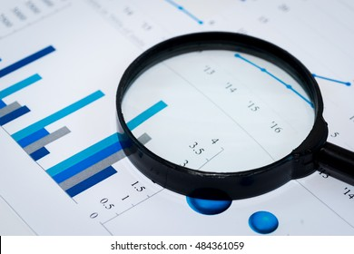Business Analysis Image - magnifying glass on graphs and spreadsheet