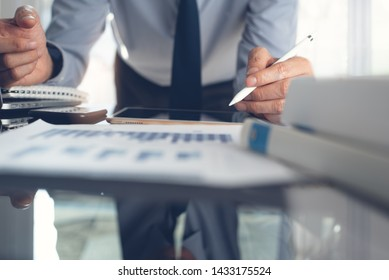 Business analysis. Business man analyzing marketing report, pointing at financial graph on digital tablet, using mobile smart phone while working on laptop computer with spreadsheet on desk in office