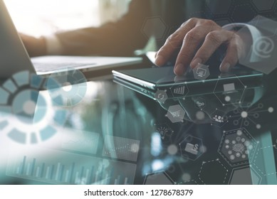 Business analysis and modern technology concept. Businessman analyzing business data on laptop computer and digital tablet at office with modern computer dashboard, marketing  report and VR icons