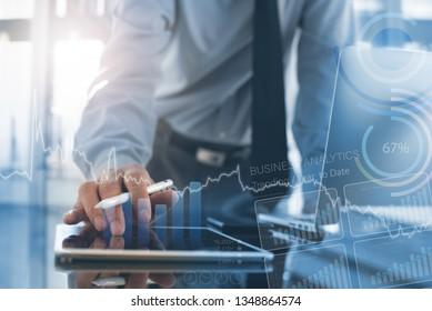 Unternehmensanalyse, modernes Technologiekonzept. Geschäftsmann, Analyse von Geschäftsdaten auf digitalem Tablet- und Laptop-Computer im Büro mit erweitertem Reality-Analytics-Computer-Dashboard auf virtuellem Bildschirm