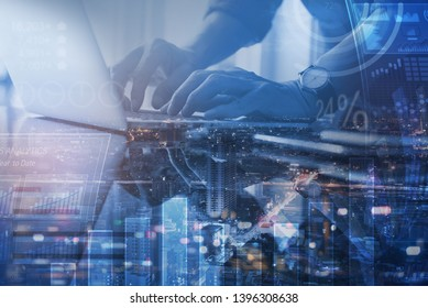 Business analysis, modern technology concept. Finance analyst working at modern office. Double exposure, business man working on laptop and the city with financial graph, computer dashboard interface