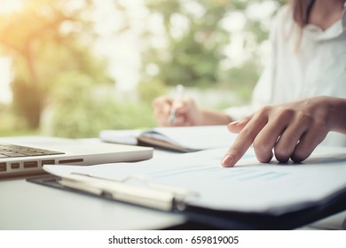 Business analysis on paper with graphs as she sits at his desk pointing to one document paper business analysis, projections and strategy concept.