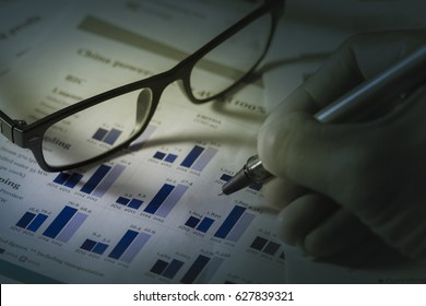 Business analysis with pen and glasses
