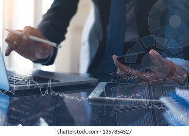 Business analysis and technology concept. Multitasking businessman, finance analyst analyzing marketing report, using digital tablet, electronic pen and laptop computer in office with financial graph