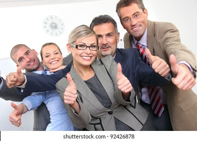 Business approval - team of colleagues with thumbs up sign