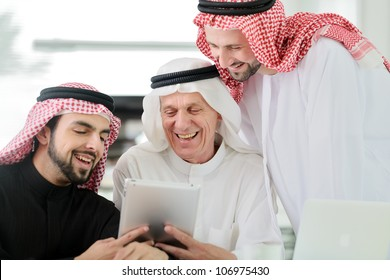 Business Arabic people at meeting indoor with electronic tablet laughing