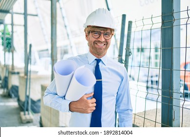 Business architect man wearing hardhat standing outdoors of a building project