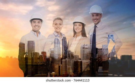 business, architecture and building concept - happy team of architects in white hard hats over city background with double exposure
