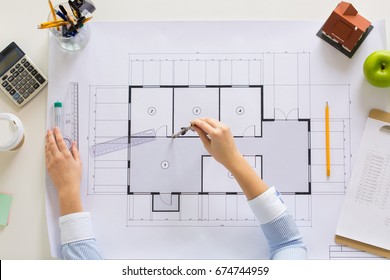 business, architecture, building and construction concept - architect hands with compass measuring blueprint of living house at office