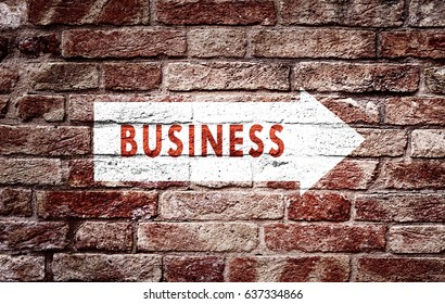 Business arrow sign on aged brick wall background. Conceptual company direction symbol.