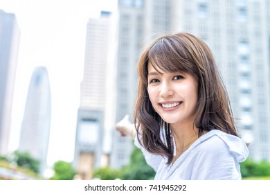 Business asian woman outdoor showing city skyline.