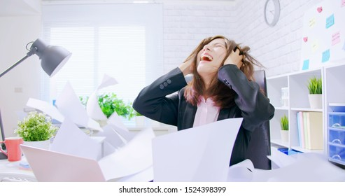 Business asian woman stressed and overworked yelling in office with rainy documents