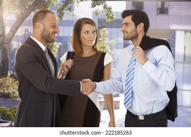 Business associates shaking hands on the street in front of bank center building.