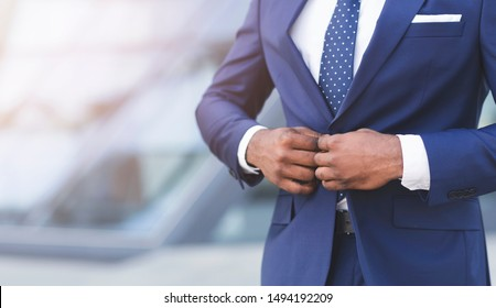 Business Attire. Unrecognizable Black Businessman Fastening Suit Jacket Standing In Urban Area. Empty Space, Cropped