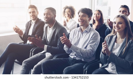 Business audience applauding to speaker at conference, listening leader