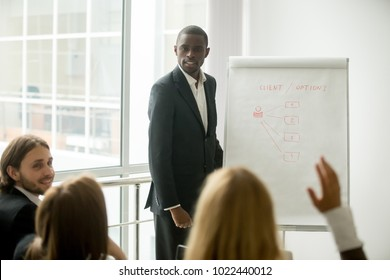 Business audience asking african american presenter speaker questions at training, black coach in suit presenting marketing project for sales team answering questions at seminar, corporate education