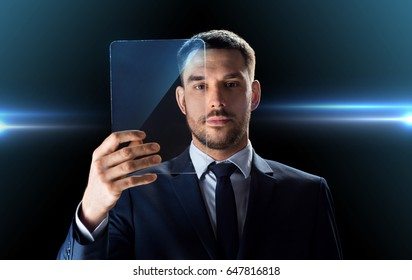 business, augmented reality and future technology concept - businessman in suit working with transparent tablet pc computer over black background