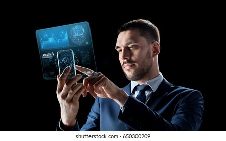 business, augmented reality and future technology concept - businessman working with transparent smartphone and virtual screens projections over black background