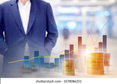 Business background blur of asian aged 40 to standing in black suit, walkway Inside the building there are people. Foreground is graphs, statistics Indicates the positive direction and empty space .