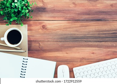 Business background concept. Closeup of coffee cup, notepad, keyboard and mouse on wood table with free space.