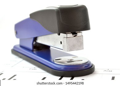 Business background with graph and stapler on white.