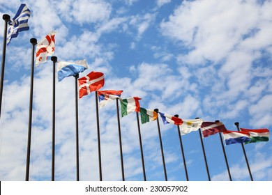 business background of international flags on a background cloudy sky