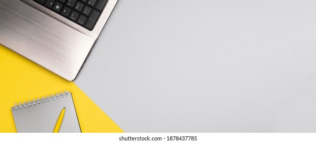 Business background with laptop and notepad. Minimal stylish workspace in new color of the year 2021: Ultimate gray and Illuminating yellow. Top view, flat lay, copy space, banner
