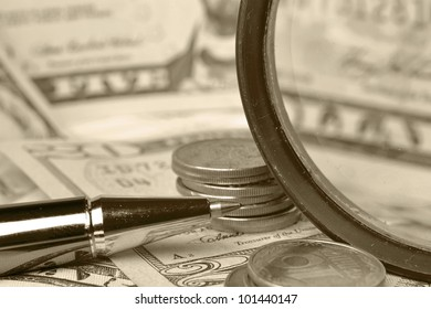 Business background with magnifier, coins and pen.