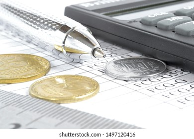 Business background with pen, calculator, coins and table.