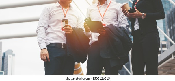 business background of business people with coffee cup and smartphone on hands standing together outdoor in city and having business discussion