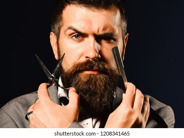 Business and barbershop service concept. Businessman with strict face on dark blue background. Man with beard holds shaving razor and scissors. Macho in formal suit cuts and shaves beard and moustache