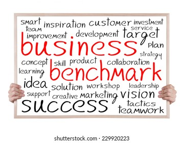 business benchmark and other related words handwritten on whiteboard with hands