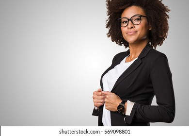 business black woman adjusting her clothes on a grey background