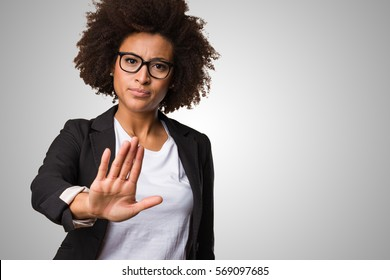 business black woman doing stop gesture on a grey background